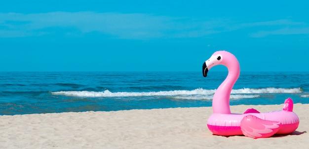 Fenicottero gonfiabile su una spiaggia sabbiosa
