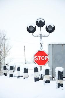 Fermare. il segnale stradale rosso è situato sull'autostrada che attraversa la linea ferroviaria nella stagione invernale