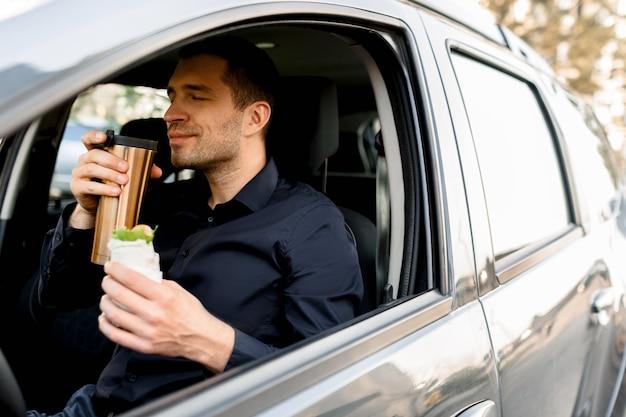 Fermarsi per mangiare un boccone. l'uomo mangia snack in macchina e beve caffè o tè.