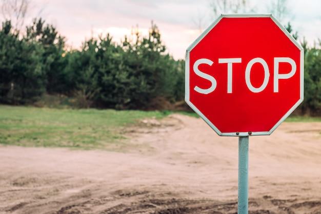 Fermata del segno sulla strada forestale vuota.