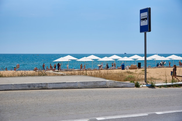 Fermata dell'autobus con un cartello sulla spiaggia del mare.