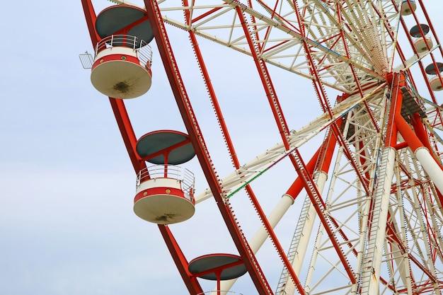 Ferris wheel rossa e bianca con cielo blu pastello