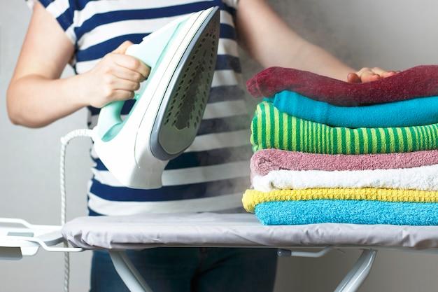 Ferro e una pila di asciugamani sull'asse da stiro