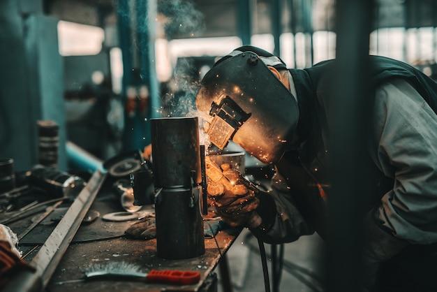 Ferro lavoratore in tuta protettiva, maschera e guanti tubo di saldatura. interno officina.