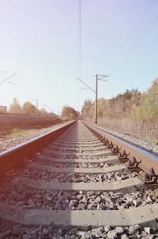 Ferrovia che retrocede nella distanza fra gli alberi di autunno verdi e gialli