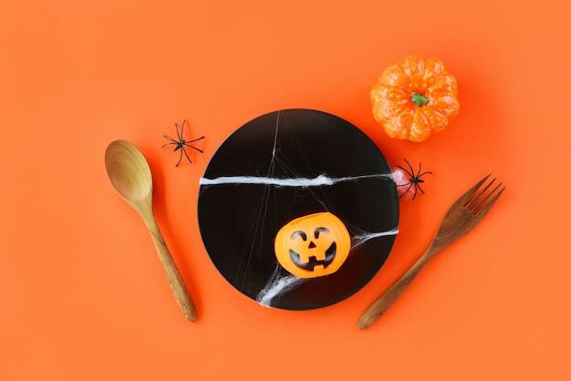 Festa degli accessori della decorazione della regolazione della tavola di halloween con la forchetta del cucchiaio del ragno e la lanterna della presa o della zucca in banda nera