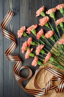 Festa del 9 maggio. garofani bracciali su fondo in legno scuro con nastro di san giorgio.