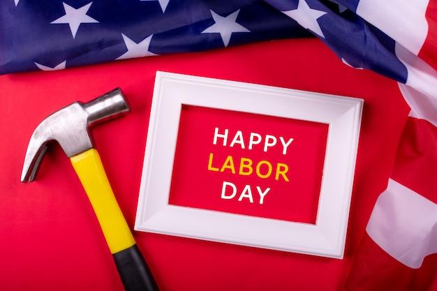 Festa del lavoro concetto usa, martello e cornice bianca su sfondo di carta rossa con bandiera degli stati uniti.
