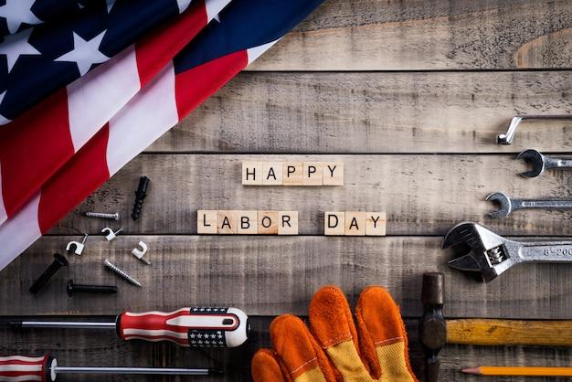 Festa del lavoro, usa bandiera america con molti strumenti a portata di mano su fondo di legno