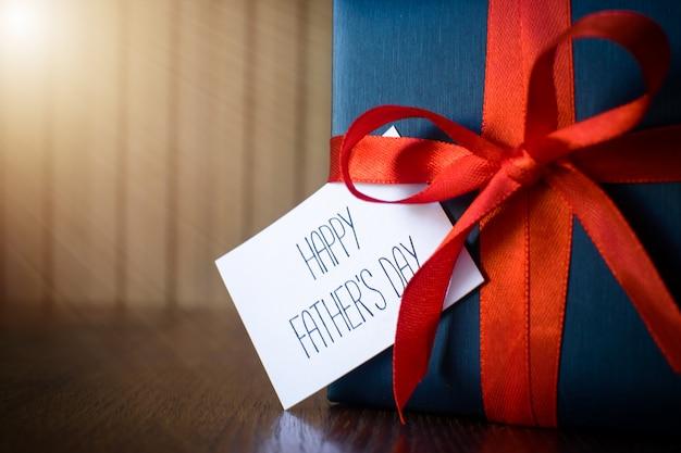 Festa del papà. pacchetto regalo avvolto con carta blu e corda con un nastro rosso su fondo di legno