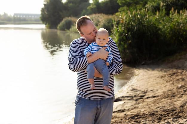 Festa del papà. papà bacia figlio felice stile di vita familiare. family look per attività ricreative all'aperto. giornata di sole sul fiume