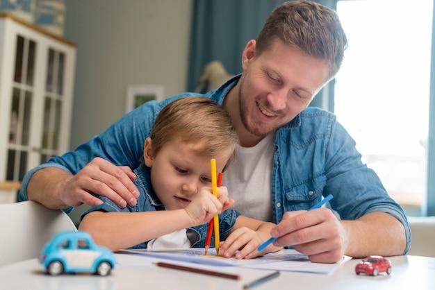 Festa del papà papà e figlio che colorano un libro
