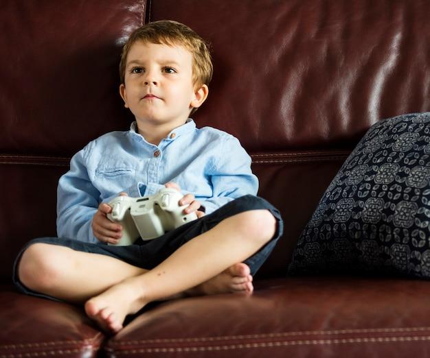Festa del ragazzo che gioca gioco che si siede sul sofà a sua casa