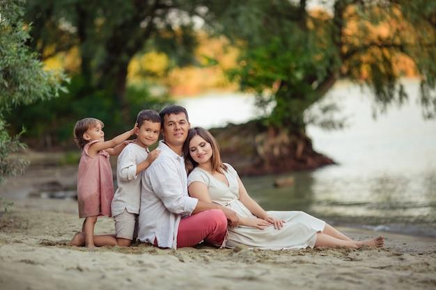 Festa della famiglia, genitori felici. mamma, papà, figlio e figlia si divertono a passeggio. sono seduti sulla sabbia vicino al fiume