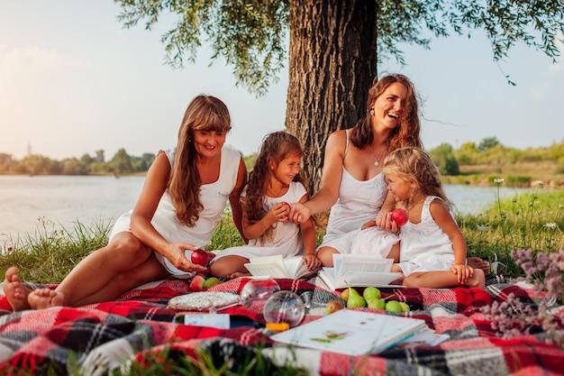 Festa della mamma. famiglia che ha picnic dal fiume di primavera. madre, nonna e bambini che ridono.