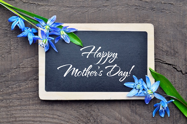 Festa della mamma felice lavagna e primi fiori della molla su vecchio fondo di legno carta greting di festa della mamma.
