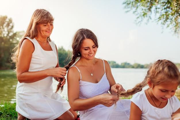 Festa della mamma. madre, nonna e figlia intrecciano l'un l'altro i capelli. famiglia divertendosi sul picnic