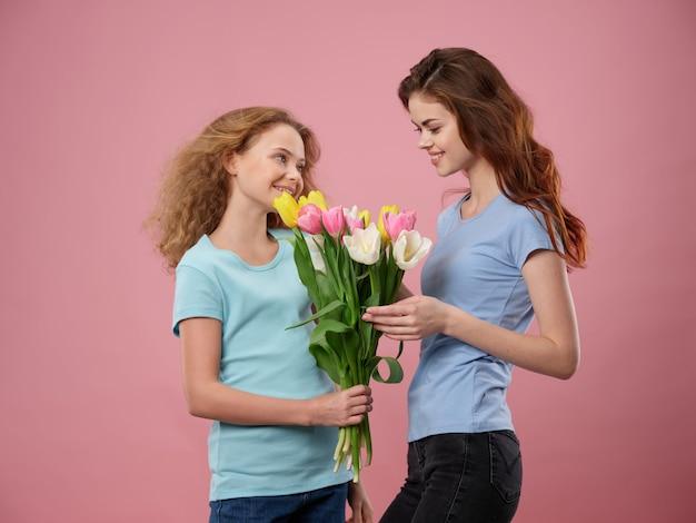 Festa della mamma, una giovane donna con un bambino in posa con fiori, un regalo per la festa della donna e la festa della mamma