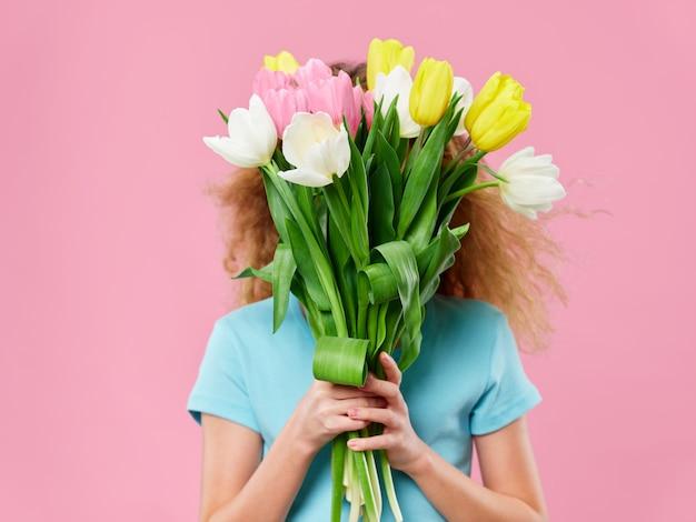 Festa della mamma, una giovane donna con un bambino in posa con fiori, un regalo per la festa della mamma