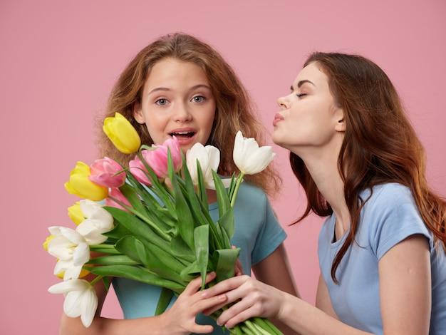 Festa della mamma, una giovane donna con un bambino in posa in studio con fiori, un regalo per la festa della donna e la festa della mamma