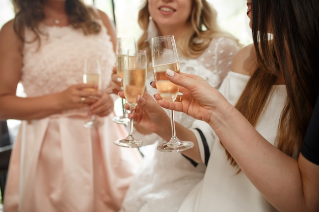 Festa delle ragazze le ragazze allietano i bicchieri con lo champagne nel ristorante.