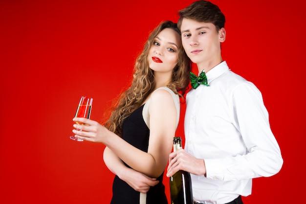 Festa di capodanno concetto felice divertimento sorridente amici coppia hipsters festeggia l'inverno vacanze di natale indossando il costume da fiaba carnevale cravatta a farfalla tenendo in vetro champagne bottiglia saluti