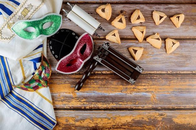 Festa di carnevale ebraico tradizionale celebrazione di purim e biscotti hamantaschen, fabbricatore di rumori e maschera, libro sacro, talit, kippa