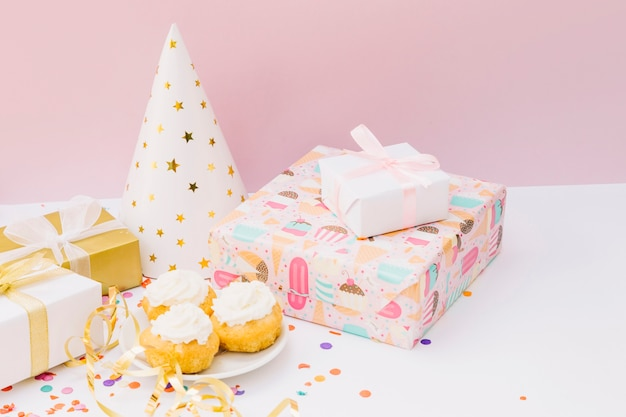 Festa di compleanno con cupcake; scatole regalo e cappello da festa sulla scrivania bianca