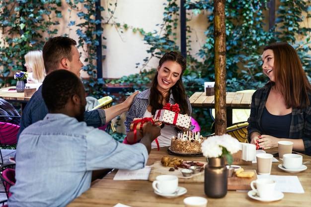 Festa di compleanno di una ragazza sulla terrazza di un caffè con regali dai migliori amici