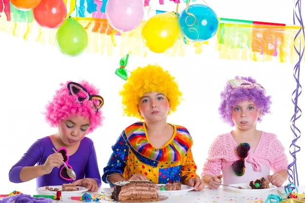 Festa di compleanno felice dei bambini che mangia la torta di cioccolato