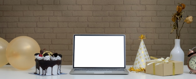 Festa di compleanno online con laptop, torta, confezione regalo, palloncini e cappello da festa