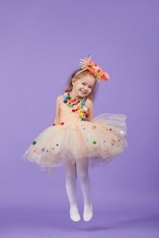 Festa di compleanno per bambini, in maschera. piccola ragazza felice del bambino del bambino in un vestito operato dal tutu gonfio, divertendosi sullo spazio viola. spazio per il testo