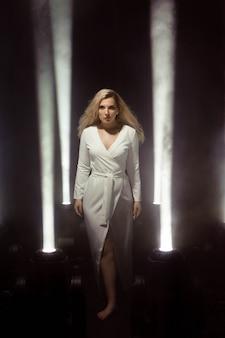 Festa di luci club donna ragazza che balla capelli lunghi. taglie forti artista che posa in un fascio di luce sul palco.