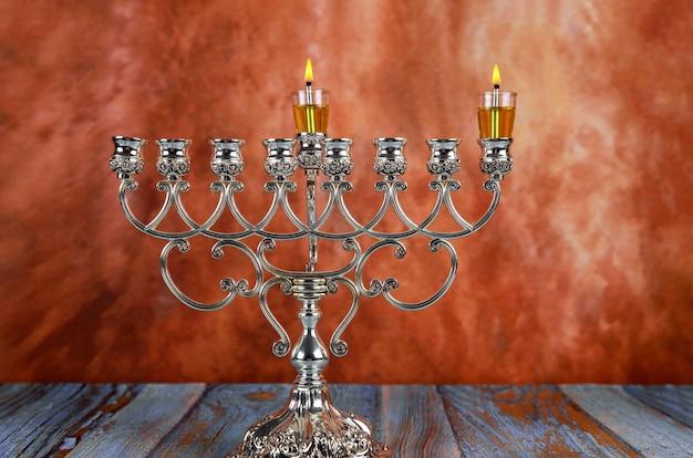 Festa ebraica di hanukkah con l'accensione della prima candela su un candelabro tradizionale menorah di hanukkah