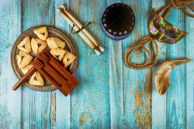 Festa ebraica purim con biscotti hamantaschen orecchie hamans, maschera di carnevale e kippa pergamena, corno