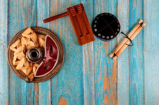 Festa ebraica purim con biscotti hamantaschen orecchie hamans, maschera di carnevale e pergamena kippa, corno, su fondo rustico