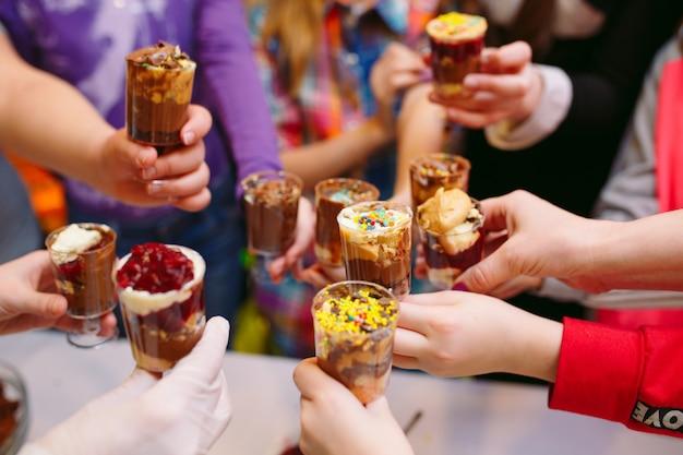 Festa per bambini. bambini che tengono cupcakes nei bicchieri.