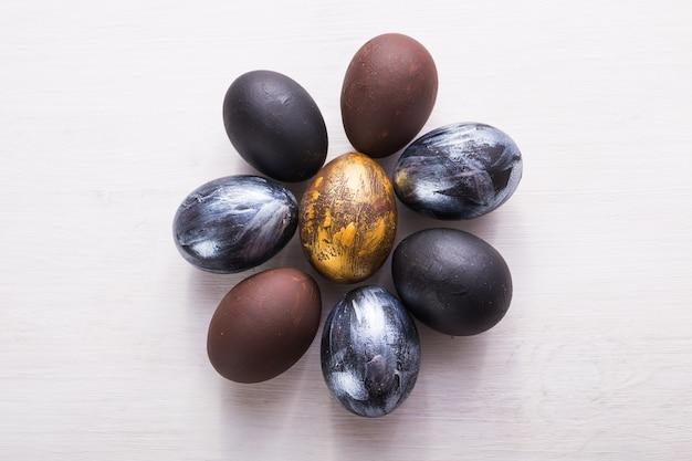 Feste, tradizioni e concetto di pasqua - uova di pasqua alla moda scure su fondo di legno bianco.