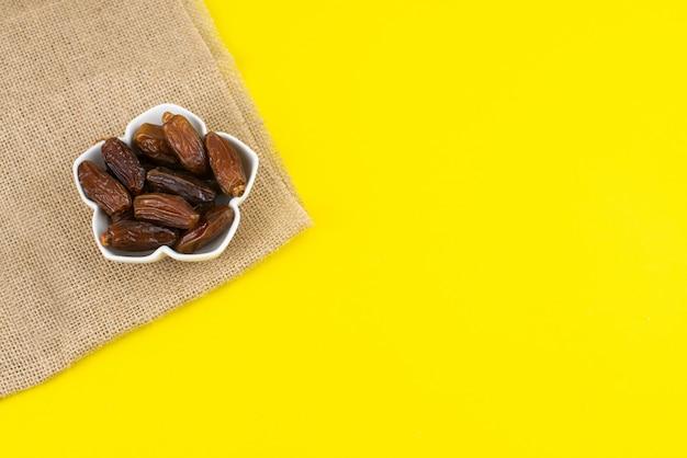Festival del ramadan kareem. chiuda su della frutta dei datteri secchi in ciotola su fondo giallo. copia spazio.