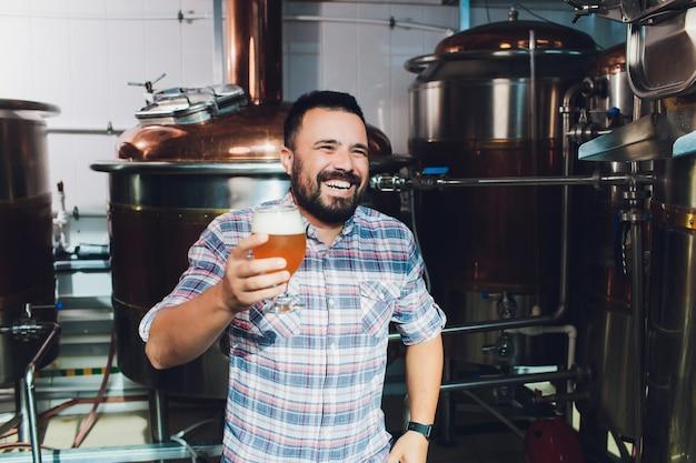 Festival dell'oktoberfest. degustazione di birra fresca prodotta. il birraio tiene il bicchiere con birra artigianale. concetto di birrificio. uomo con birra della tazza. alcol. il birraio maschio tiene il bicchiere con la birra. festa di oktober barman. brewer.