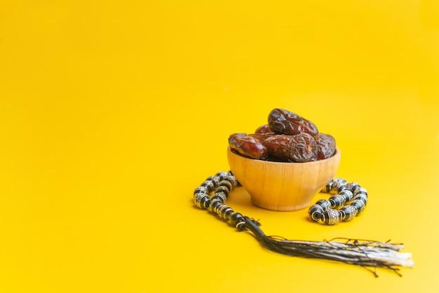 Festival di ramadan kareem, date alla ciotola di legno con il rosario su fondo giallo