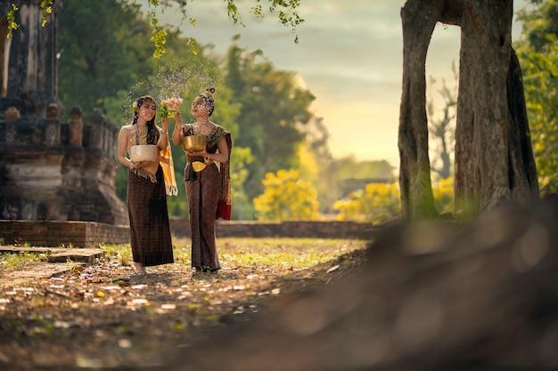 Festival di songkran due giovani donne stanno spruzzando acqua e partecipando a una tradizione del capodanno thailandese chiamata songkran day.