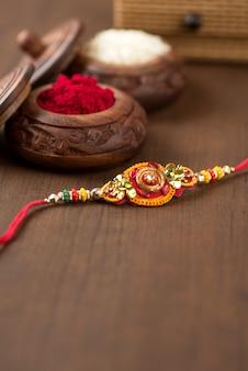 Festival indiano: celebrazione di raksha bandhan con un elegante rakhi, rice grains e kumkum. un tradizionale cinturino da polso indiano che è un simbolo di amore tra fratelli e sorelle.