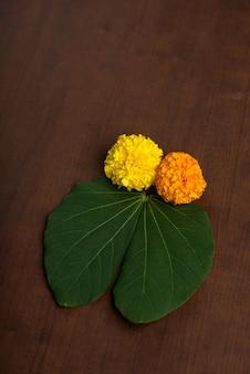 Festival indiano dussehra, che mostra foglie dorate e fiori di calendula su brown.