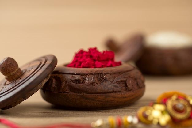 Festival indiano: raksha bandhan con un elegante rakhi, rice grains e kumkum. un tradizionale cinturino da polso indiano che è un simbolo di amore tra fratelli e sorelle.
