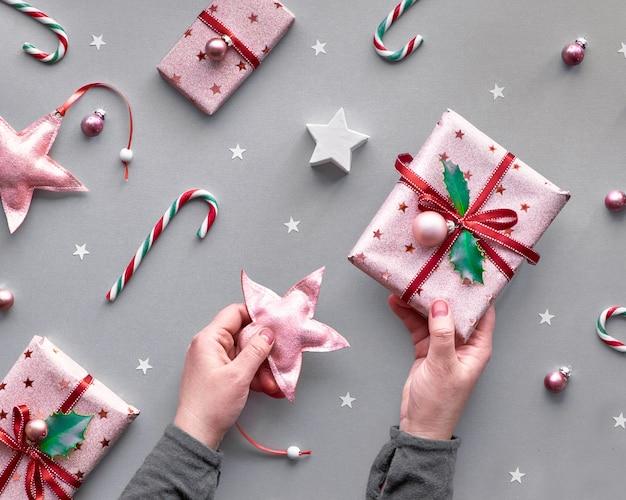 Festivo tono di natale bicolore con scatole regalo rosa, bastoncini di zucchero a strisce, bigiotteria e stelle decorative, piatto creativo geometrico posato su carta argentata in rosa e magenta