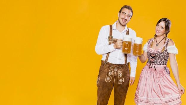 Festivo uomo e donna con boccali di birra