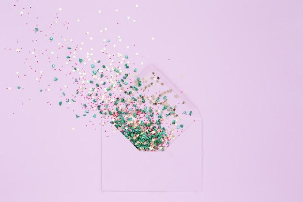 Festosa esplosione di coriandoli dalla busta su sfondo lilla