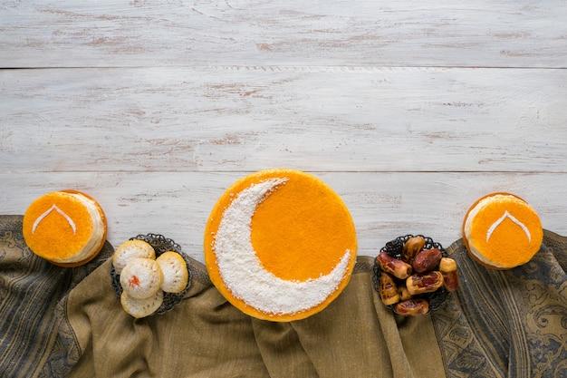 Festosa parete del ramadan. deliziosa torta dorata fatta in casa con una falce di luna, servita con datteri. vista dall'alto.