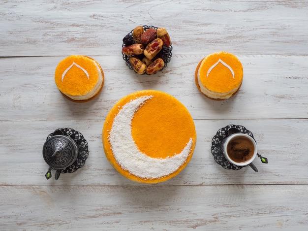Festosa parete del ramadan. deliziosa torta dorata fatta in casa con una luna crescente, servita con caffè nero e datteri